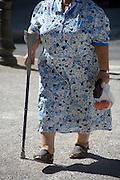 elderly woman using a crutch as a walking stick