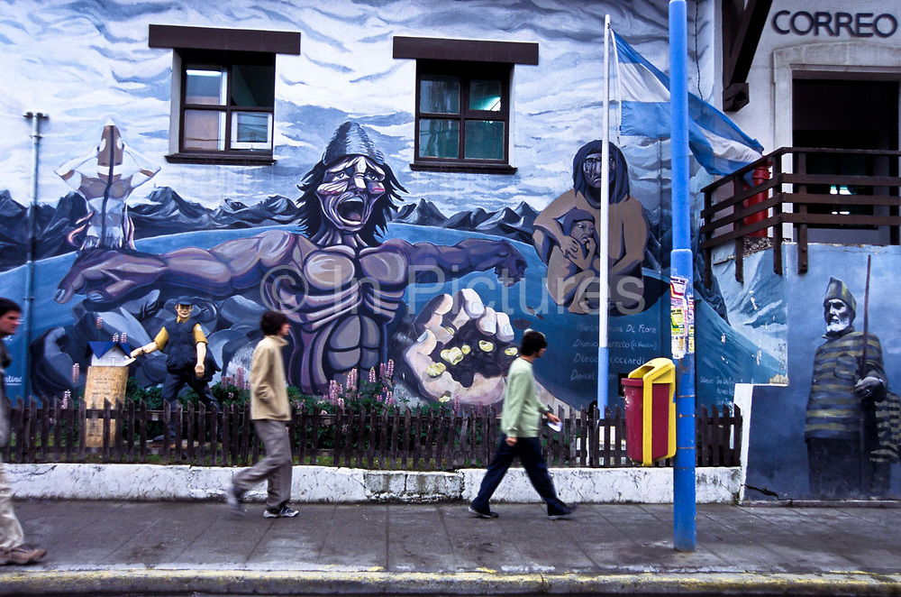 A painted mural on the post office building in Ushuaia city, Santa Cruz province, Patagonia depicting the history of this remote land. The slaughter of the Indian population, the prisoners in the southernmost jail in the world, which reputedly included the Tango crooner, Carlos Gardel as inmates, Tierra del Fuego, Argentina