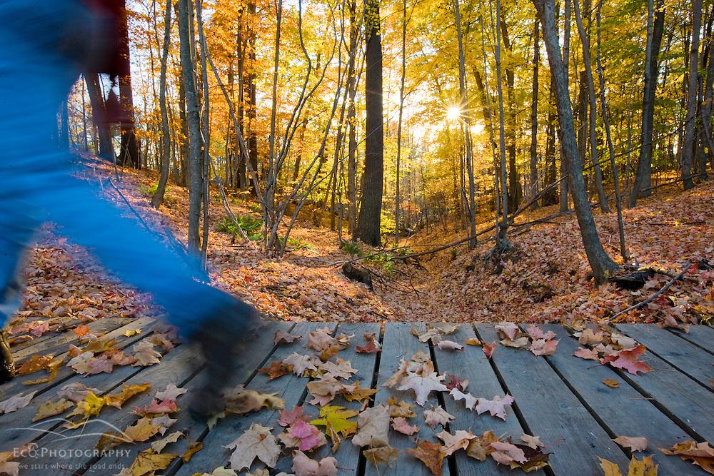 A man hikes over a footbridge near the Presumpscot River in Portland, Maine. Fall.  Model Released.