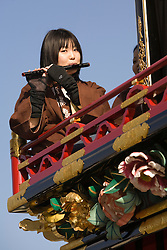 Asia, Japan, Gifu prefecture, Takayama (also known as Hida-Takayama), teenage girl playing flute on elaborate festival float (yatai)  in Gonjunko Procession during Sanno Festival of Hie Jinja Shrine, held annually in April.