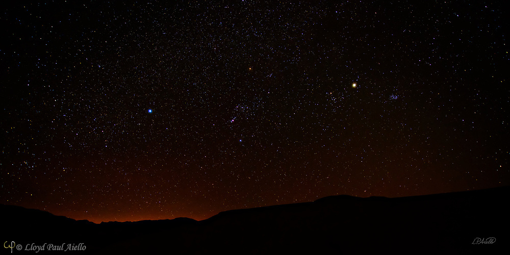 In the winter at Death Valley, the clear skies, cold nights and lack of nearby lights create one of the best viewing environments for the night sky.  Seen here in March, the many colors of the stars are clearly visible.  Centered in the image is the constellation Orion, with Orion's Belt and sword clearly visible.  Orion is observable worldwide in the evening sky from January to March.  It was named after Orion, a hunter in Greek mythology.  The earliest depiction of the constellation of Orion is a prehistoric (Aurignacian) mammoth ivory carving found in a cave in the Ach valley in West Germany in 1979. Archaeologists have estimated it to have been fashioned approximately 32,000 to 38,000 years ago<br /> <br /> Orion's Belt (or The Belt of Orion) consists of the three bright stars: Zeta (Alnitak), Epsilon (Alnilam), and Delta (Mintaka). Alnitak is approximately 800 light years away from earth and is 100,000 times more luminous than the Sun, although much of its radiation is in the ultraviolet range which the human eye cannot see. Alnilam is approximately 1,340 light years away from Earth and is 375,000 times more luminous than the Sun. Mintaka is 915 light years away and is 90,000 times more luminous than the Sun, and is a double star.  <br /> <br /> The Pleiades star cluster (also known as the Seven Sisters or M45) is visible from virtually every place on Earth and is one of the nearest star clusters. It can be seen from as far north as the north pole, and farther south than the southernmost tip of South America. It looks like a tiny misty dipper of stars, shown here 3/4 of the way to the right and halfway up in the sky.  In both myth and science, the Pleiades are considered sibling stars. The Pleiades stars were born from the same cloud of gas and dust about 100 million years ago. The cluster of several hundred stars is about 430 light-years distant, and the sibling stars drift through space together at about 25 miles per second. Many of these Pleiades stars shine
