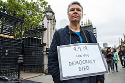 """London, UK. 11 September, 2019. A pro-Remain protester outside Parliament wears a sign reading """"9.9.19 The Day Democracy Died"""" in reference to the proroguing of Parliament by Prime Minister Boris Johnson's Government."""