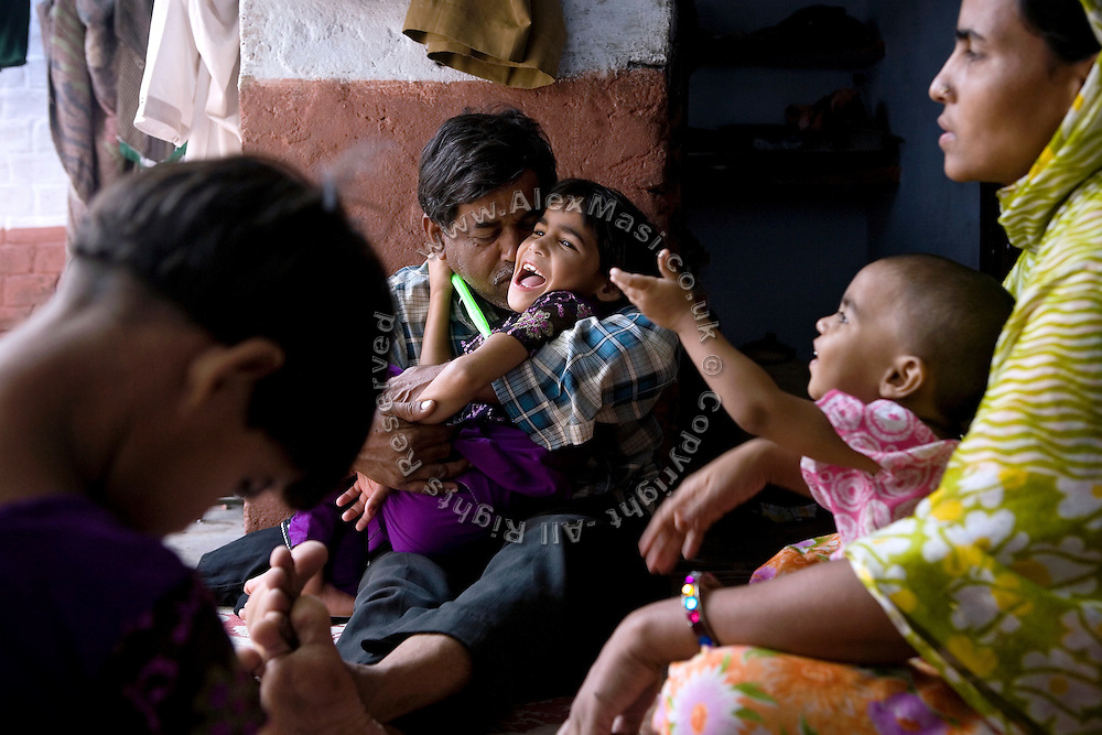Fozia, 7, is smiling in the arms of her father while sitting with her family and twin sister Shazia, (left) in their home inside the impoverished Nawab Colony, Bhopal, Madhya Pradesh, located dangerously near the abandoned Union Carbide (now DOW Chemical) industrial complex. Both girls are affected by severe neurological disorders.