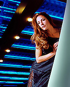 A model at night under the neon lights of a skybridge to an office building in Salt Lake City, UT