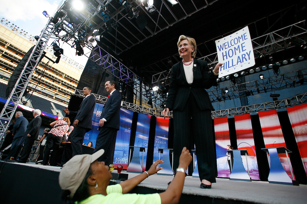 """Senator Hillary Rodham Clinton (D) of New York, a native of Park Ridge, Illinois, holds up a """"Welcome Home Hillary"""" sign given to her by a supporter during a commercial break at an AFL-CIO Working Families Presidential Candidates Forum at Soldier Field in Chicago Tuesday evening."""