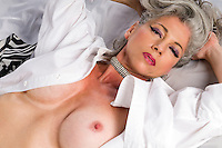 Very attractive woman at her fifities laying nude in bed.