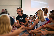 Linsey Corbin, professional triathlete from Missoula, MT, gets high-fives from a mock finish line crowd of kids in the Boys and Girls Club at Mullan Trail Elementary on Thursday.