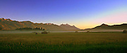 A cold August morning in 2011 after the first cutting of hay<br /> sets the scene against a cobalt blue sky and the sunrise. Mist wanderer the Hayfield as the sun rays light up the tips of the Tetons.