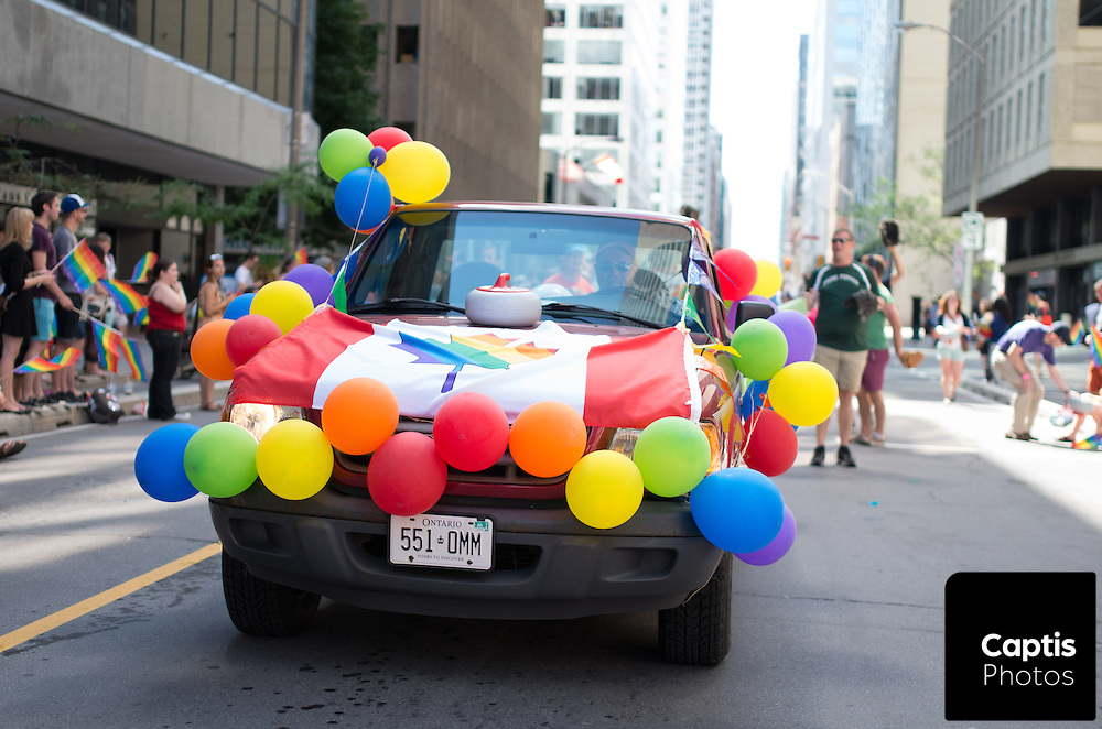 A vehicle decorated with balloons and a flag drives with the parade. August 24, 2014.