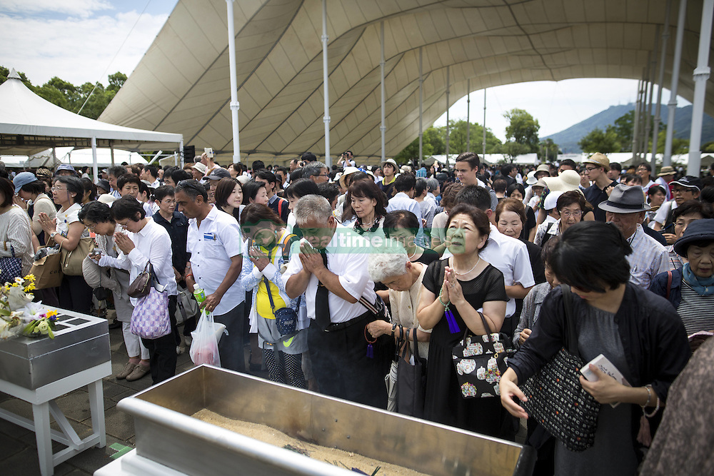 August 9, 2016 - Nagasaki, Nagasaki Prefecture, Japan - NAGASAKI, JAPAN - AUGUST 9 : Visitors lays flowers and pray for the atomic bomb victims in front of the Peace Statue in Nagasaki Peace Park, Nagasaki, southern Japan, Tuesday, August 9, 2016. Japan marked the 71st anniversary of the atomic bombing on Nagasaki. On August 9, 1945, during World War II, the United States dropped the second Atomic bomb on Nagasaki city, killing an estimated 40,000 people which ended World War II. (Credit Image: © Richard Atrero De Guzman/NurPhoto via ZUMA Press)
