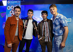 (left to right) Kevin Jonas, Nick Jonas and Joe Jonas of the Jonas Brothers join Capital FM presenter Roman Kemp in the on air studio during Capital's Summertime Ball. The world's biggest stars perform live for 80,000 Capital listeners at Wembley Stadium at the UK's biggest summer party.