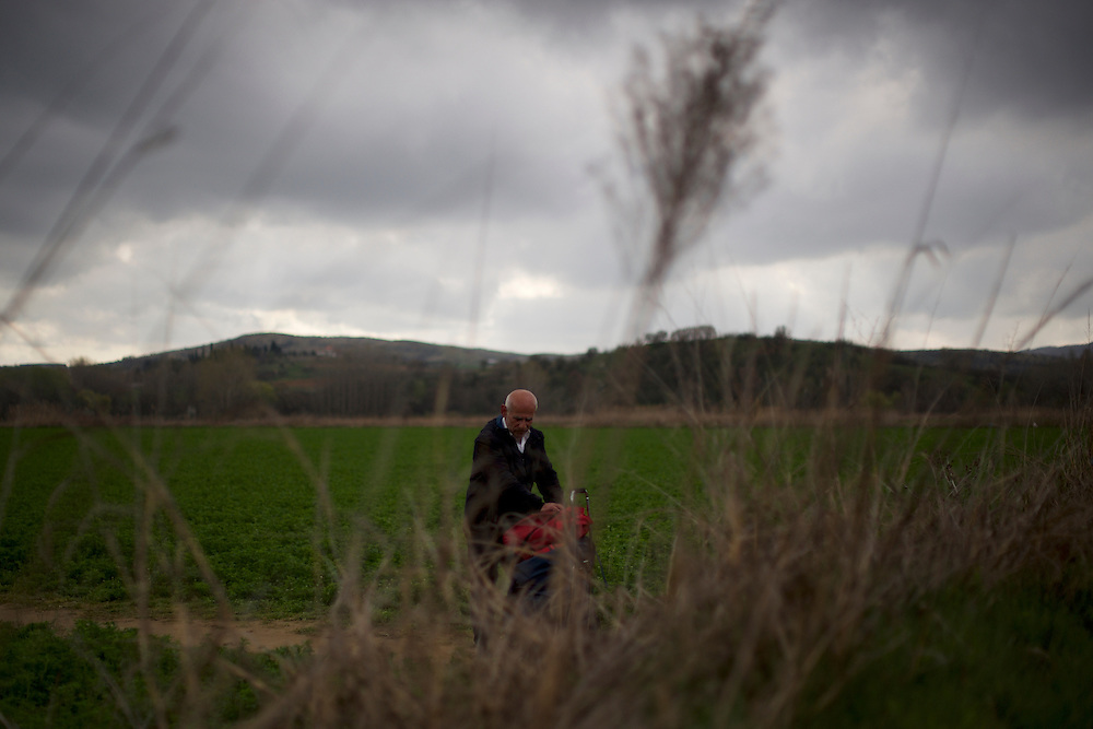 A Syrian-kurdish man walks through a field on his way towards the Greek-Macedonian border station of Idomeni, Greece.