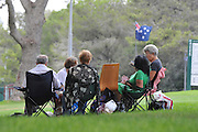 A group of mature people sit on chairs in the park