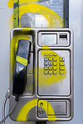 A detail of a public BT landline phone kiosk has been vandalised by the spraying of yellow aerosol paint over its handset and keypad on the Southbank in Waterloo, on 11th March 2021, in London, England.