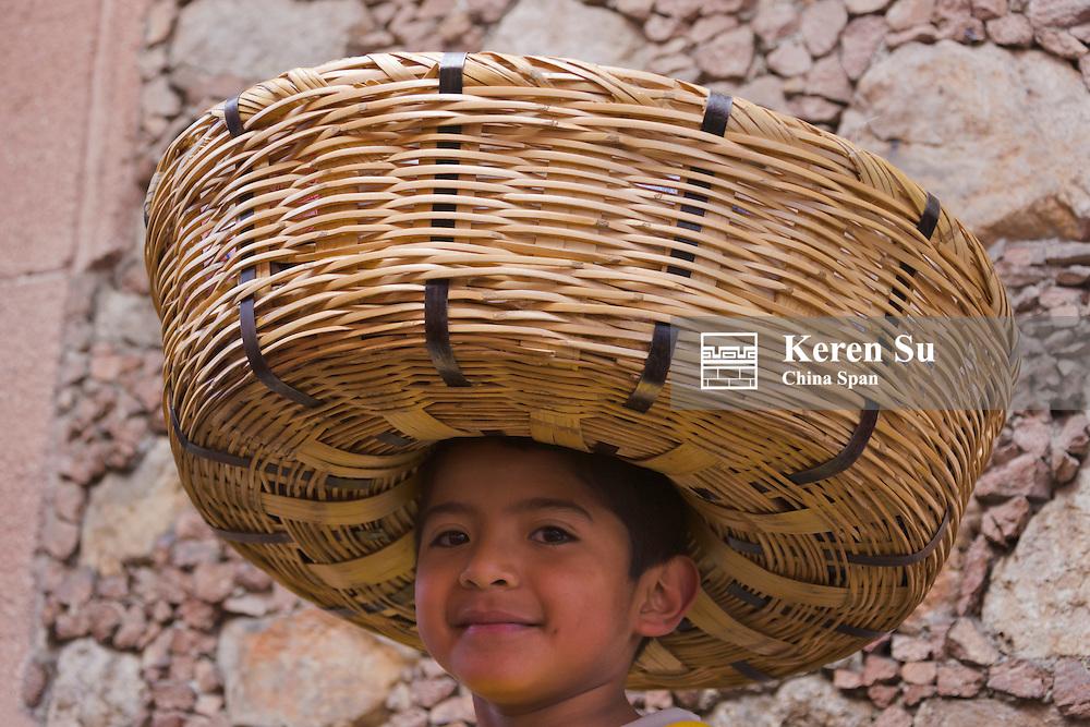 Boy carring basket of tortillas, Zitacuaro, Mexico