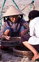 Old woman wearing a conical hat sorting fish.