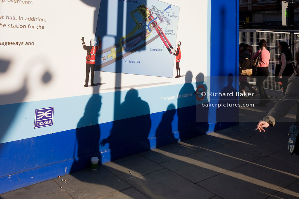 A smoker and anonymous peoples' shadows with a London Crossrail construction site hoarding.