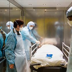 Extrait du reportage au long cours Covid19 ce que veut dire être soignant publié aux éditions Byakko en décembre 2020. <br /> Suivi du quotidien des équipes de l'hôpital d'instruction des armées Bégin de Saint-Mandé pendant la première vague de l'épidémie de coronavirus en France. Pendant 3 mois, la photographe a partagé le quotidien des personnels de garde : infirmières, aide-soignants, médecins, manipulateurs-radio, etc. au sein des différents services consacrés aux victimes du Covid-19. <br /> <br /> Avril-Juillet 2020 / Saint-Mandé (94) / FRANCE<br /> <br /> Dans le monte-malade, les brancardiers et l'officier de permanence descendent au -2 pour emporter au dépositoire le corps d'un patient décédé de la Covid en fin de journée. <br /> <br /> Découvrir le livre Covid19 ce que veut dire être soignant https://byakko.fr/boutique/livre-covid19-ce-que-veut-dire-etre-soignant/<br /> Voir plus de photos de ce reportage (55 photos) https://sandrachenugodefroy.photoshelter.com/gallery/2020-04-Covid19-ce-que-veut-dire-tre-soignant/G0000_uUmPCIj7oo/C0000yuz5WpdBLSQ