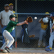 A young first base player catches the ball to get the out at first during the Norwalk Little League baseball competition at Broad River Fields,  Norwalk, Connecticut. USA. Photo Tim Clayton