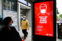 © Licensed to London News Pictures. 22/05/2020. London, UK. A woman wearing a face covering at a bus stop in north London looks at a 'WEAR A FACE COVERING ON PUBLIC TRANSPORT' digital poster, which is a part of the London for Transport's public information campaign as the lockdown is eased. Photo credit: Dinendra Haria/LNP