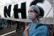 October 9th 2011. Blockade of Westminster Bridge organised by UK Uncut before the NHS bill goes before Parliament on October 12th. A young woman dressed as a nurse stands next to a banner saying NHS.