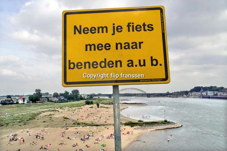 Nederland, Nijmegen, 1-8-2020 Een warme dag in de zomer . Mensen trekken naar de oevers van de waal en de spiegelwaal in het rivierpark aan de overkant van Nijmegen . De meesten komen met de fiets via de fietsbrug de snelbinder . Hier laten ze de fiets achter wat gevaarlijke situaties oplevert op het fietspad van de brug . De gemeente heeft een bord geplaatst om mensen op te roepen de fietsen mee naar beneden te nemen . De warmte, hoge temperatuur, drijft mensen naar het water . Het is verboden in de rivier te zwemmen vanwege de stroming en het drukke scheepvaartverkeer . . Vanwege de coronadreiging moet afstand gehouden worden, maar vooral jongeren, jonge mensen, zitten soms in groepen bij elkaar . Foto: ANP/ Hollandse Hoogte/ Flip Franssen