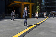 A lunchtime office worker walks and talks seemingly unaware of the trip hazard ahead - a yellow line covering hazardous electrical cabling at Leadenhall in the City of London, (aka The Square Mile) the capital's financial district, on 2nd September 2019, in London, England.