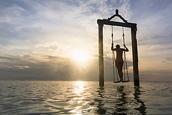 Rear view of young man standing on rope swing at beach against sunset, Gili Trawangan, Lombok, Indonesia