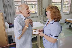 Rehabilitation assistant supervising elderly patient doing exercises to keep shoulder mobile,