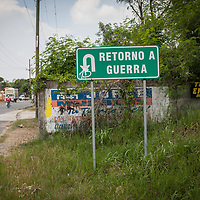 A street sign says retorno a Guerra (return to war).