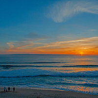 Friends watch a sunset over the Pacific Ocean from Montara State Beach, California.
