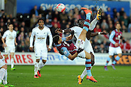 Aston Villa's Rudy Gestede  tries an overhead kick at goal as Swansea's Bafetimbi Gomis blocks. Barclays Premier league match, Swansea city v Aston Villa at the Liberty Stadium in Swansea, South Wales on Saturday 19th March 2016.<br /> pic by  Carl Robertson, Andrew Orchard sports photography.