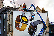 Erecting mural advertising Apple smart watches on Great Eastern Street, Shoreditch, London.