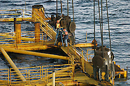 KEVIN BARTRAM/The Daily News.Workers open valves to release air from the legs of an El Paso Corporation offshore platform about 100 miles south of Galveston on Tuesday, June 28, 2005. The air, which had been used for buoyancy, was released to allow the platform to sink to the bottom of the Gulf of Mexico to form an artificial reef.