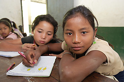 Unnamed children, (no age given) study in this small school at the end of a long dusty road. Teenpha village, Pha Oudom District, Bokeo Province, Lao PDR