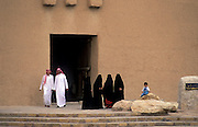 Saudi men, four wives and a young boy outside the Fort of Al Masmak