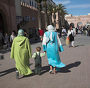 Two women walking in the street hand in hand with a child Essaouira, Morocco