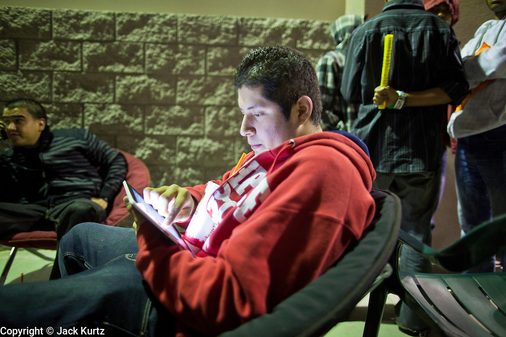 """24 NOVEMBER 2011 - PHOENIX, AZ: 22:53 Liborio Luna (CQ) plays on his iPad and drinks a Jamba Juice while he waits for the store to open at the Best Buy store on Thunderbird and I 17 in Phoenix. He said he wasn't looking for anything in particular and was out to """"play with my iPad and have a Jamba Juice."""" """"Black Friday,"""" the unofficial start of the holiday shopping season started even earlier than normal. Many stores, including Target and Best Buy, opened at midnight. The Best Buy at Thunderbird and I 17 showed a Harry Potter movie on the side of a rented truck in the parking lot to keep people amused while they waited for the store to open.   Photo by Jack Kurtz"""