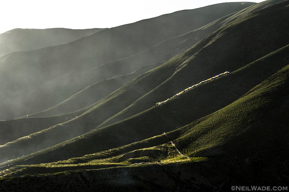Tibetan Buddhist prayer flags blow in the wind on a mountainside near Yushu, Tibet.