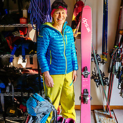 Portrait of Martha Hunt in her garage with her quiver of ski gear.