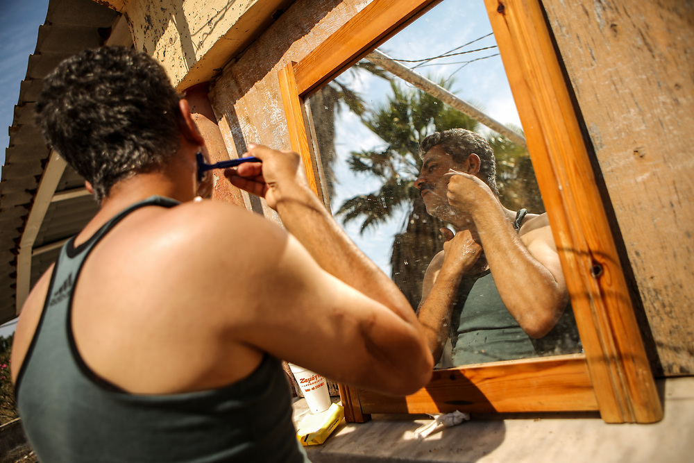 A Palestinian refugee shaves with cold water at the Hotel Captain Elias in Kos, Greece on July 1, 2015. Supplies such as shaving razors are brought in by local residents and sometimes tourists.