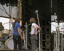 Phil Lesh and un-ID crew member in conversation on stage before the Grateful Dead Play Live at Dillon Stadium, Hartford, CT 31 July 1974. Featuring the Wall of Sound. Summer weekday show, one of the longest ever played by The Dead. Deadheads hanging out, Crew setting up.