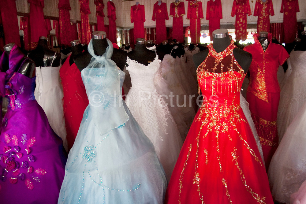 Colourful wedding dresses for sale at a wedding dress shop in De Hui city, Jilin Province. North Eastern China.