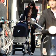 NLD/Amsterdam/20070328 - Irene van de Laar wandelend in de lentezon met haar zoon Vince in de wandelwagen door Amsterdam