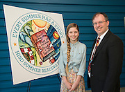 Texas Connections Academy eighth grader Maggie Martin, left, and Chief Academic Officer Dan Gohl, right, pose for a photograph with Martin's winning artwork to promote the Houston ISD Summer Reading Program, April 25, 2014.