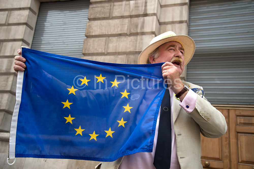 On 2nd anniversary of Brexit , June 23rd 2018, around 100,000 people marched in Central London demanding a People's Vote on the final Brexit deal.  A well-dressed man in a blazer and Panama hat holds up a European flag.