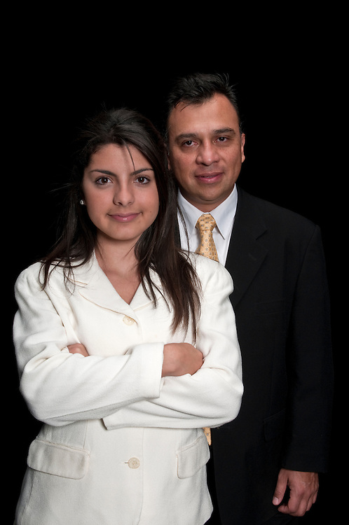 Hispanic team of boss and secretary standing on black background.