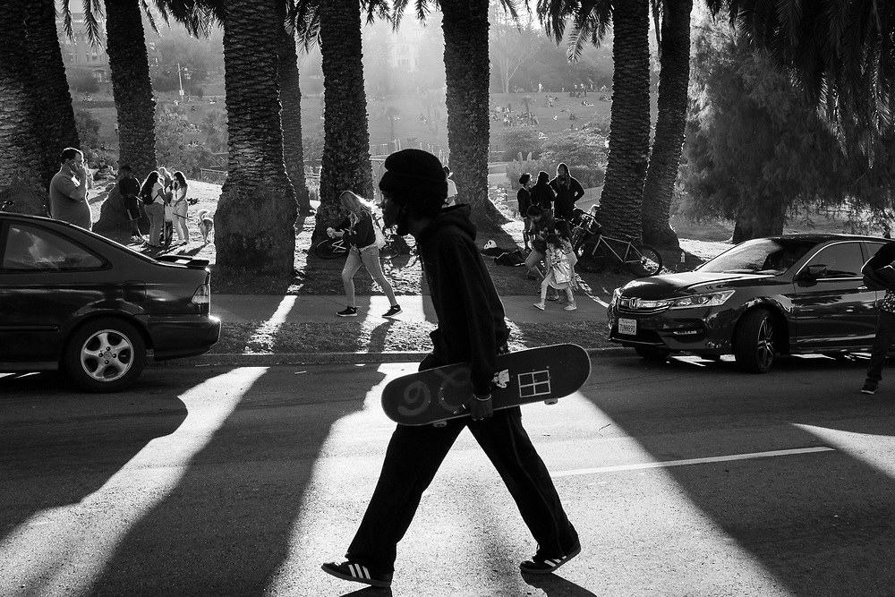 """A man carries his skateboard up Dolores Street in San Francisco, CA on July 11th, 2020 during an annual Dolores Hill skateboarding event. The annual """"hill bombing"""" has drawn hundreds of skateboarders who skate down one of San Francisco's longest hills."""