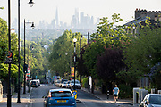 With the London skyline in the far distance, a runner descends the steep gradient of Gypsy Hill in Crystal Palace, on 16th June 2021, in London, England.