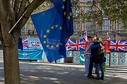On the day that the EU in Brussels agreed in principle to extend Brexit until 31st January 2020 (aka 'Flextension') and not 31st October 2019, Remainers hug in front of Brexit Party flags and banners during a Brexit protest outside parliament, on 28th October 2019, in Westminster, London, England.